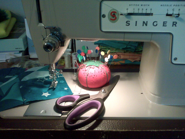 my old Singer sewing machine, a few pins in a tomato pin cushion, a pair of scissors, and a piece of the quilt I'm working on.