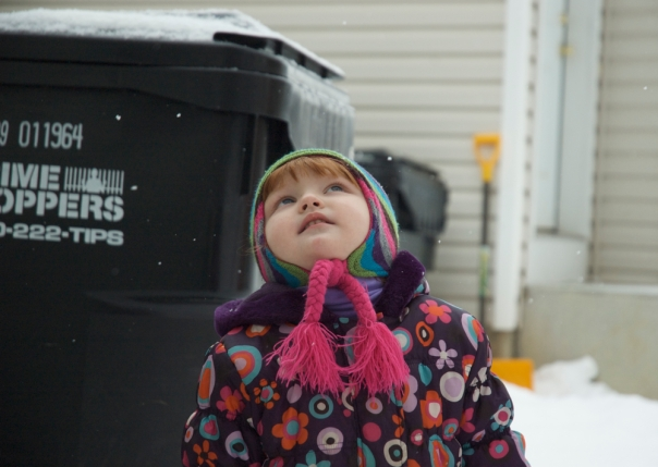 a little girl, full of awe and wonderment over the falling snow