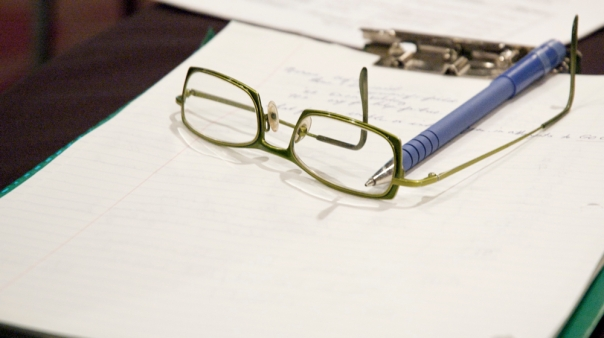 glasses, a pen, and a clipboard
