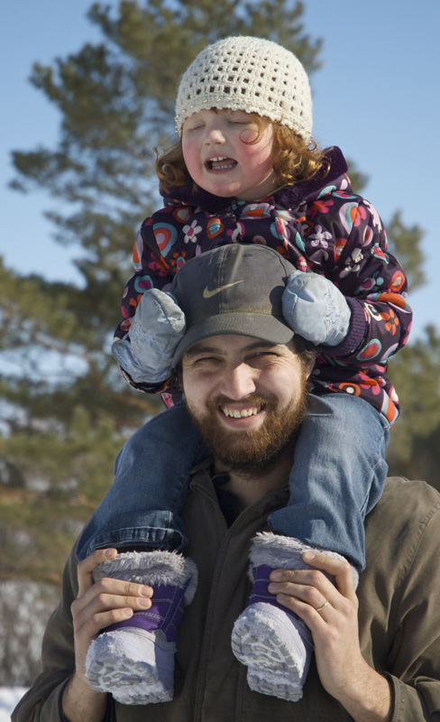 Happy Daddy carrying his wee girlie on his shoulders