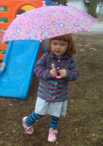 girl in the rain, holding a pink umbrella