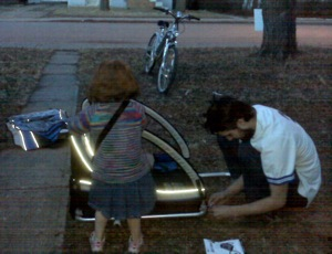 wee girlie and her daddy putting the new bike trailer together