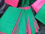 a whole pile of red and green gift bags numbered from 1 to 24