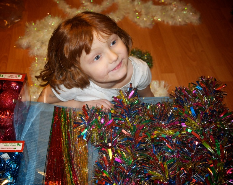 The girl, her face all filled with light and wonder, as we prepare to decorate the tree.