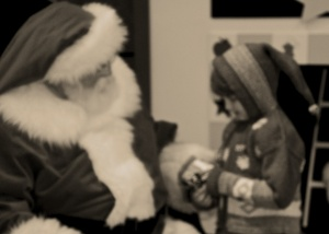 an aged black and white photograph, digitally enhanced to appear so, of the girl with Santa.