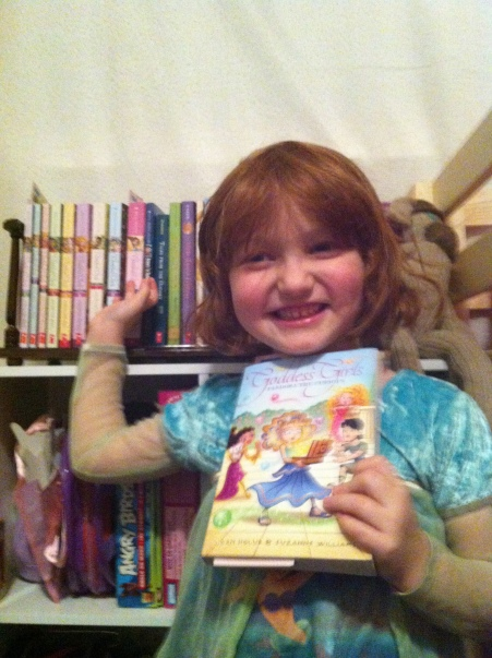 Lily-Ann (hat hair and all) proudly showing off her Goddess Girls books.