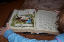 Looking at Belle's favourite book in Maurice's cottage.